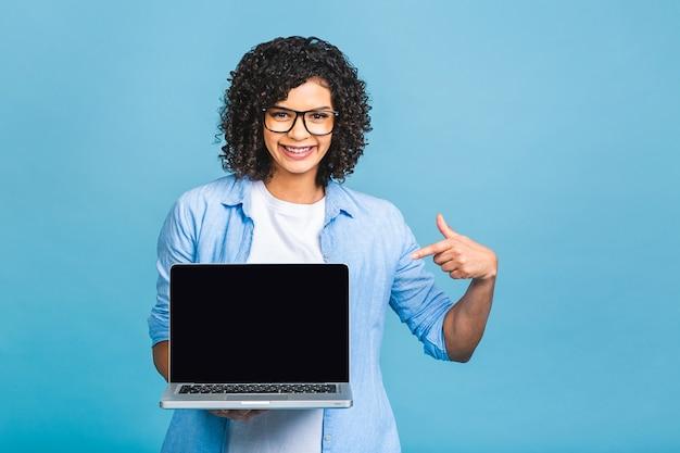 파란색 배경 위에 절연 빈 화면으로 노트북 컴퓨터를 보여주는 곱슬 머리를 가진 젊은 아프리카 아름 다운 아가씨.