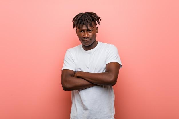 不満で顔をしかめ若いアフリカ黒人男性は、腕を組んでいます。