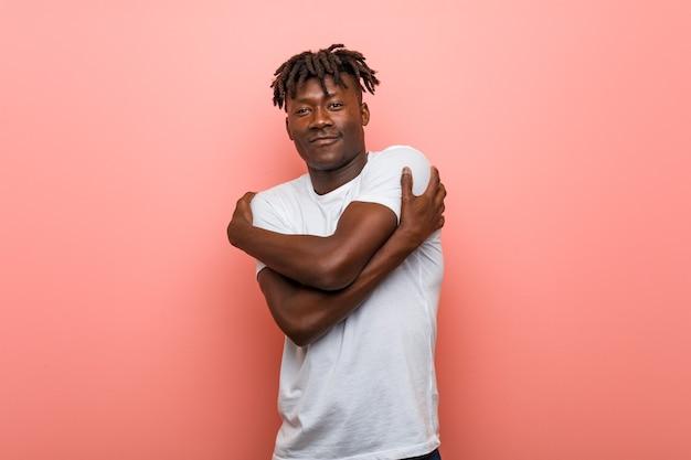 若いアフリカの黒人男性は、のんきで幸せな笑顔で自分を抱きしめます。