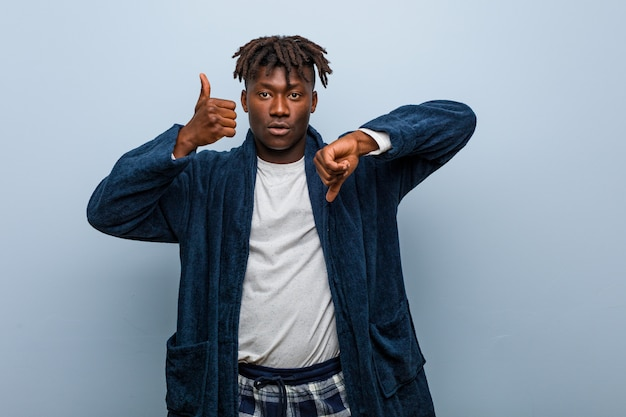 Young african black man wearing pajama showing thumbs up and thumbs down
