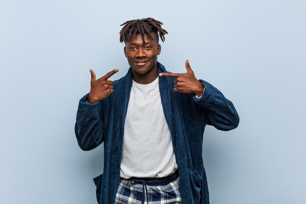 Young african black man wearing pajama smiles, pointing fingers at mouth.