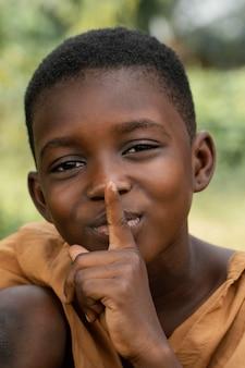 サイレントサインをしている若いアフリカの少年