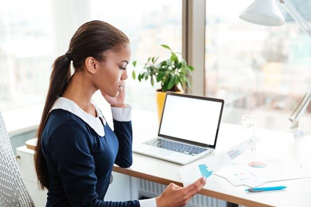 職場に座って、オフィスで電話で話しているドレスを着た若いアフリカのビジネス女性