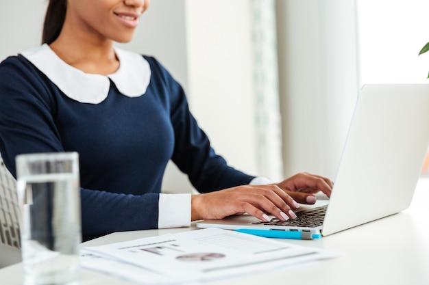 水とラップトップを使用して職場のテーブルのそばに座ってドレスを着た若いアフリカのビジネス女性。トリミングされた画像