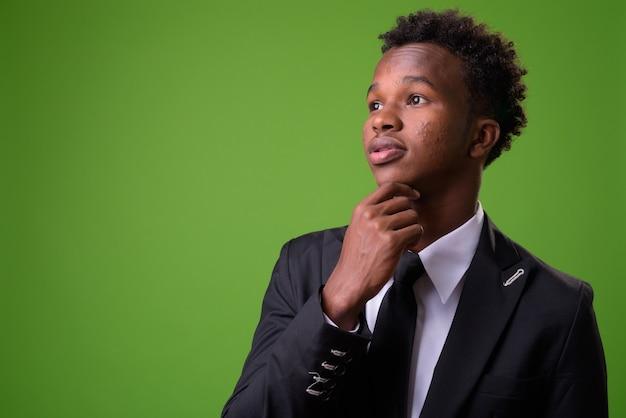 緑の壁に対して若いアフリカの実業家