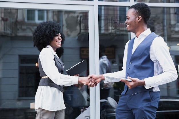 Young african businessman and businessman shaking hand in front of glass window