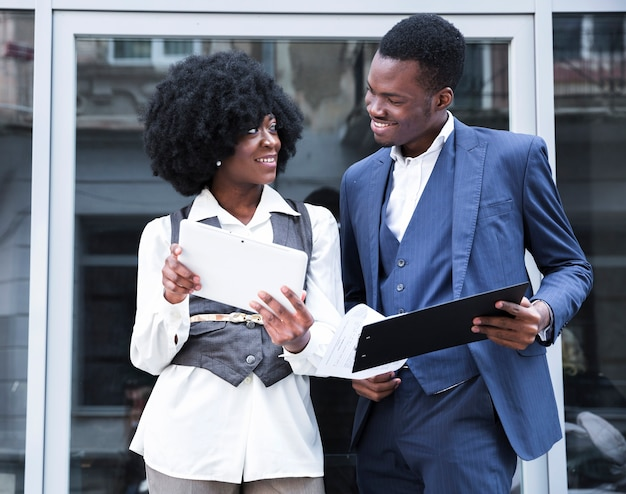Young african businessman and businesswoman holding digital tablet and clipboard looking at each other
