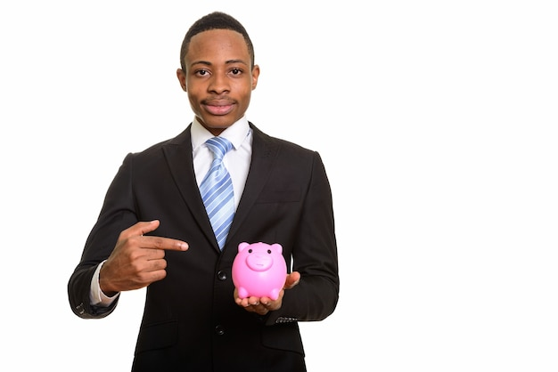 Молодой африканский бизнесмен держит копилку и указывая