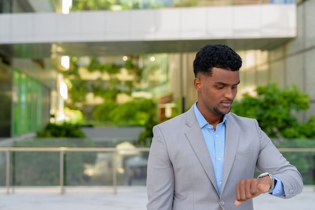Young african businessman outdoors checking time from watch