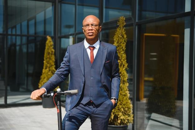 Молодой африканский бизнесмен на электросамокате