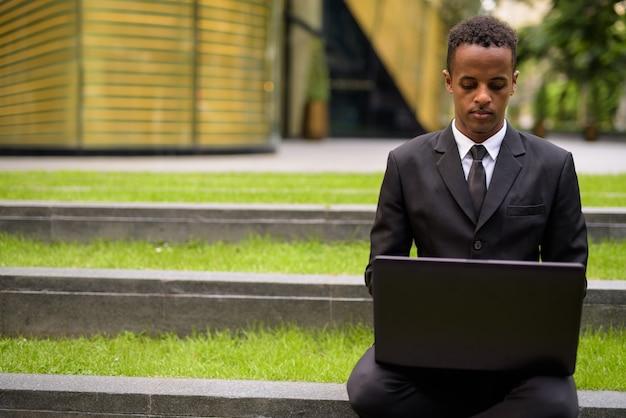 Молодой африканский бизнесмен сидит и использует портативный компьютер на открытом воздухе