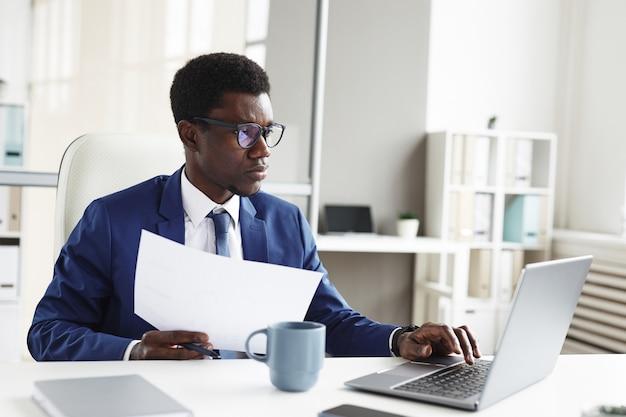 Молодой африканский бизнесмен сидит за столом перед ноутбуком, набирает документы и делает документы в офисе