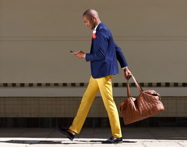 Young african businessman walking wirth bag and mobile phone
