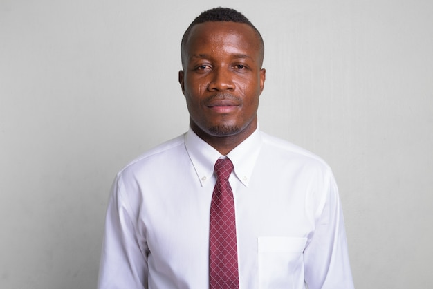 Young african businessman wearing red tie on white