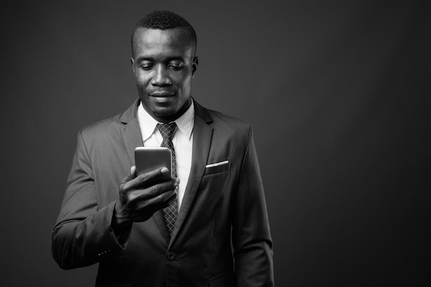 Young african businessman wearing suit against gray wall. black and white