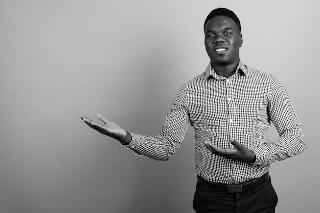 白い壁にアフロの髪を持つ若いアフリカの実業家。黒と白