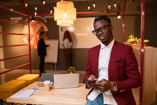 彼の2人の女性の同僚とテーブルのそばに立っている携帯電話で若いアフリカの実業家