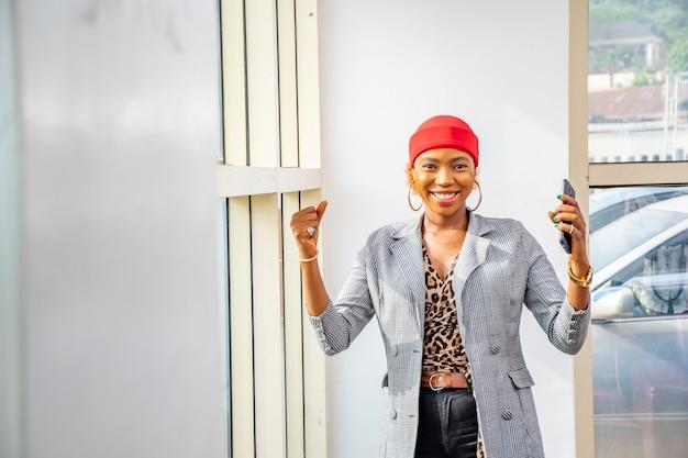 彼女の携帯電話を保持しながら祝う興奮と幸せを感じている若いアフリカの実業家
