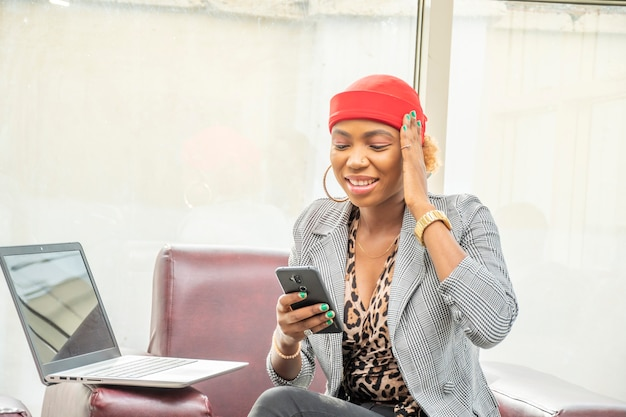 A young african businesswoman using her mobile phone feeling stressed and tired, touching her head