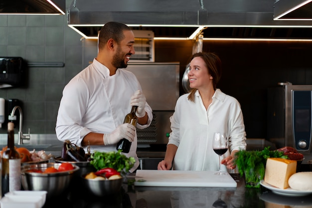 Young african chef is cooking together with caucasian girlfriend in the kitchen