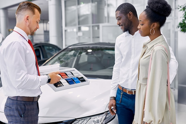 Young african clients choose colour of car in dealership