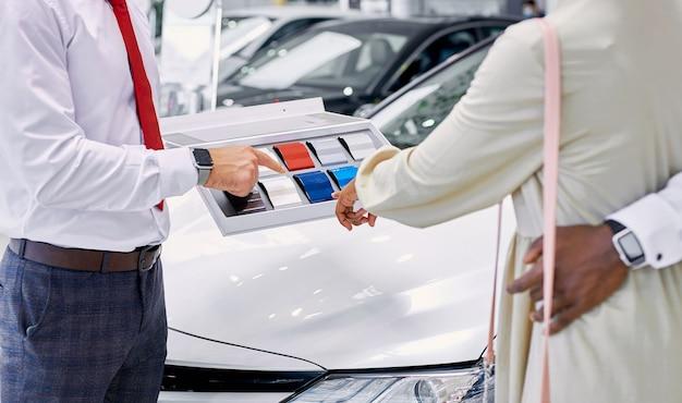 若いアフリカのクライアントはディーラーで車の色を選択します