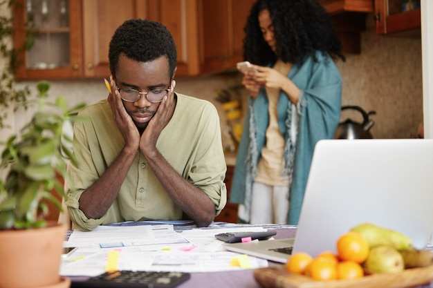 Молодая африканская пара, столкнувшаяся с финансовой проблемой, не может выплатить долги. отчаявшийся мужчина в очках, держась за щеки, чувствуя стресс, управляя семейным бюджетом за кухонным столом