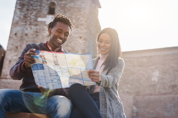 Young african couple having fun using map during holiday vacations - focus on man face