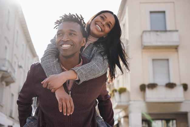 Young african couple having fun walking around the city - focus on man face
