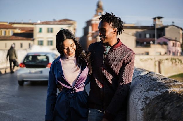 젊은 아프리카 부부는 도시를 산책하며 즐거운 시간을 보내고 있습니다 - 소녀의 얼굴에 초점