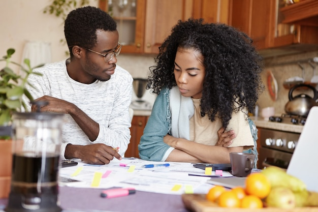 Giovane coppia africana che litiga a causa di molti debiti, seduta al tavolo della cucina con i documenti, calcolando le spese domestiche. la moglie è arrabbiata con il marito disoccupato che non è in grado di pagare le bollette