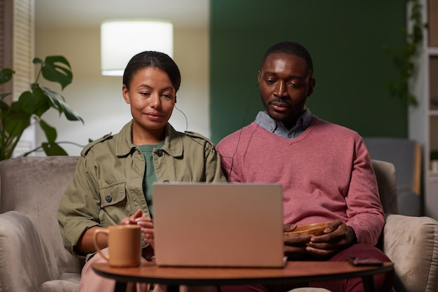 Young african couple sitting on sofa in headphones in front of laptop drinking coffee and watching movie online