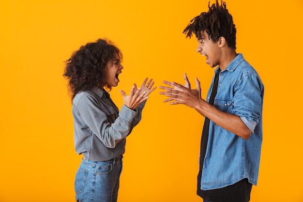 Молодая африканская пара стоя изолированно, споря