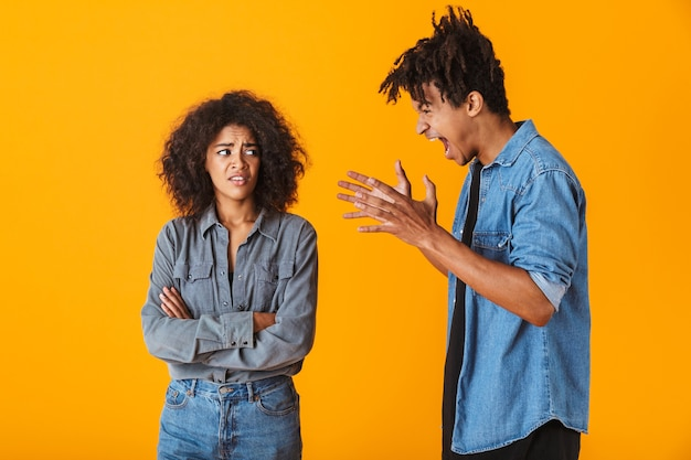 Young african couple standing isolated, having an argument