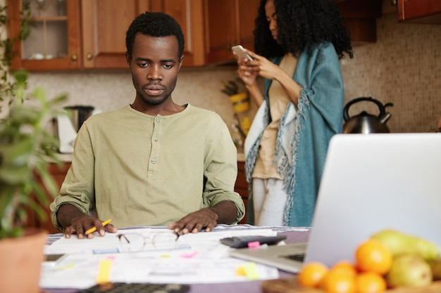 Giovani coppie africane con molti debiti che affrontano lo stress finanziario. marito pietrificato che guarda davanti a sé sconvolto, rendendosi conto che la sua famiglia non è in grado di pagare l'affitto, costretto a trasferirsi