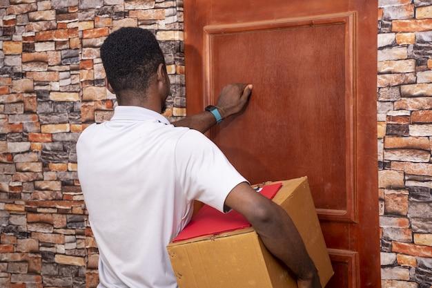 ドアをノックする若いアフリカの宅配便