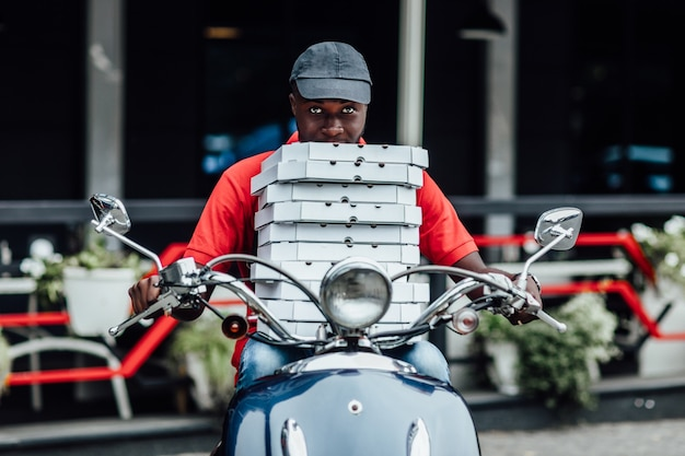 速いバイクでポーズをとる若いアフリカの宅配便は、段ボールを保持しているヘルメットを身に着けているリュックサックを運びます