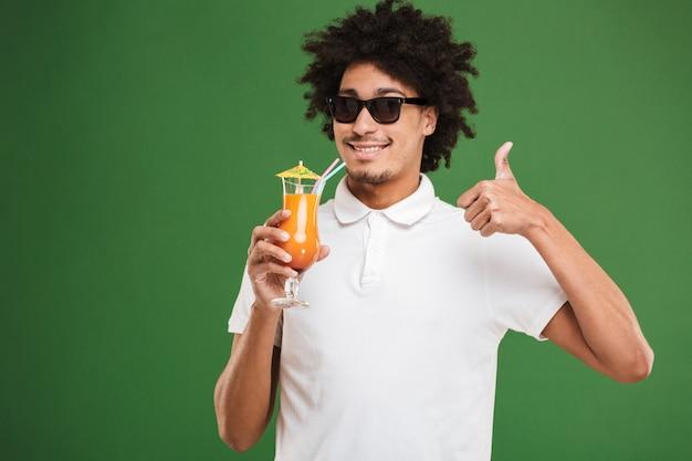カクテルを飲みながら若いアフリカの巻き毛の男。
