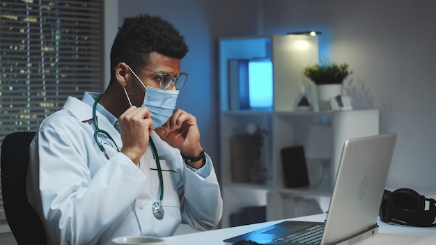 Young african doctor showing how to wear medical mask by video call on computer