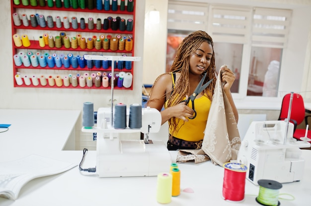 Young african dressmaker woman sews clothes on sewing machine and use scissors at tailor office. black seamstress women.