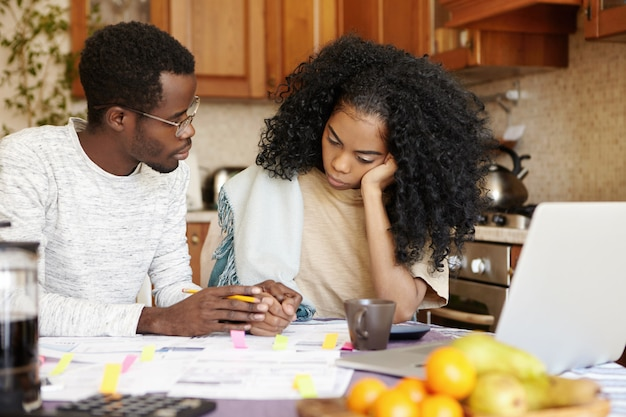 Young african family facing financial crisis. husband in glasses trying to soothe his beautiful wife, holding her hand and telling that everything will be alright while managing finances in kitchen