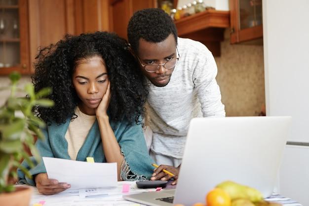 Молодая африканская семья оплачивает счета за коммунальные услуги онлайн с помощью портативного компьютера. несчастная женщина сидит за столом, анализируя лист бумаги в руке, подсчитывая домашние расходы вместе со своим мужем