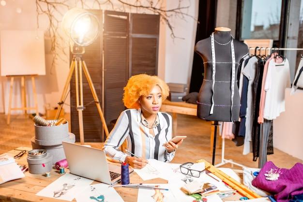 さまざまな仕立てツールでスタジオのインテリアに座って服の図面とラップトップで作業している若いアフリカのファッションデザイナー