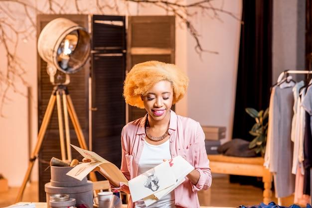スタジオのインテリアに座って服の図面とラップトップを扱う若いアフリカのファッションデザイナー