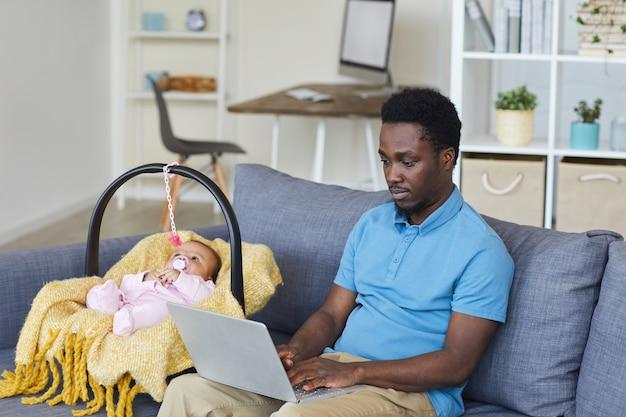 Молодой африканский отец сидит на диване и работает на портативном компьютере с ребенком, лежащим рядом в колыбели