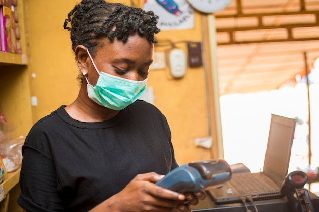 Young african female attendant using the point of sale machine to pay for the goods her customer bought while using face mask to prevent herself from the corona outbreak.