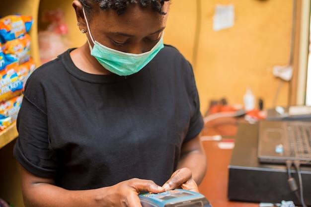 젊은 아프리카 여성 승무원은 코로나 발병을 예방하기 위해 안면 마스크를 사용하는 동안 고객이 구매한 상품에 대해 pos 기계를 사용하여 지불합니다.