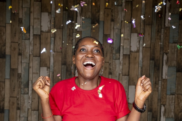 Молодая африканская женщина празднует с плавающим вокруг конфетти