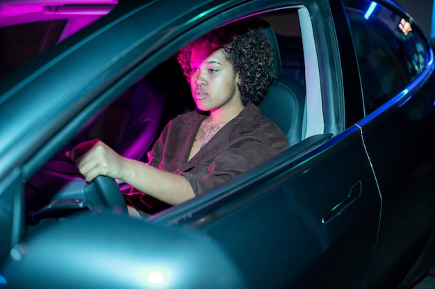 Young african female driving electric car while holding by steering wheel