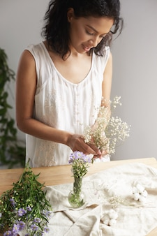 Young african female florist smiling working with bunch of flowers at workplace over white wall.